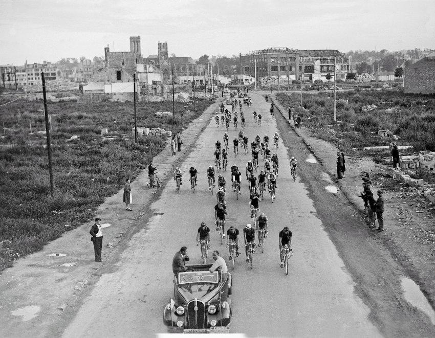 1947: Tour de France navázala 2 roky po druhé světové válce. Jezdci na fotce opouští město Caen. Poškození budov ve městě je stále patrné.