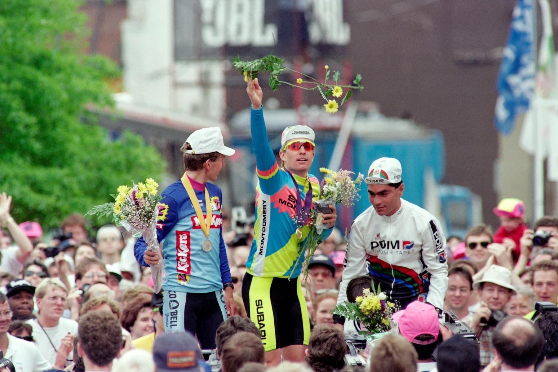 Americký cyklista Nate Reiss jako vítěz Tour de Trump 1990 hází květiny do davu diváků v Richmondu. Vlevo stříbrný Atle Kvolsvoll z Norska a vpravo třetí muž pořadí Mexičan Raul Alcala. Foto: profimedia