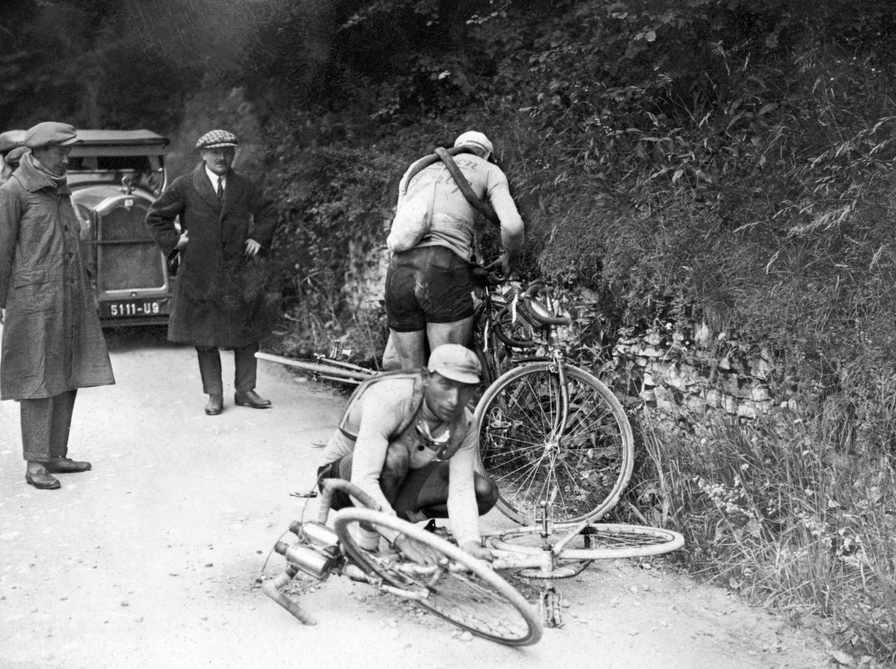 Závodníci pod dohledem rozhodčích provádí opravy na svých bicyklech.