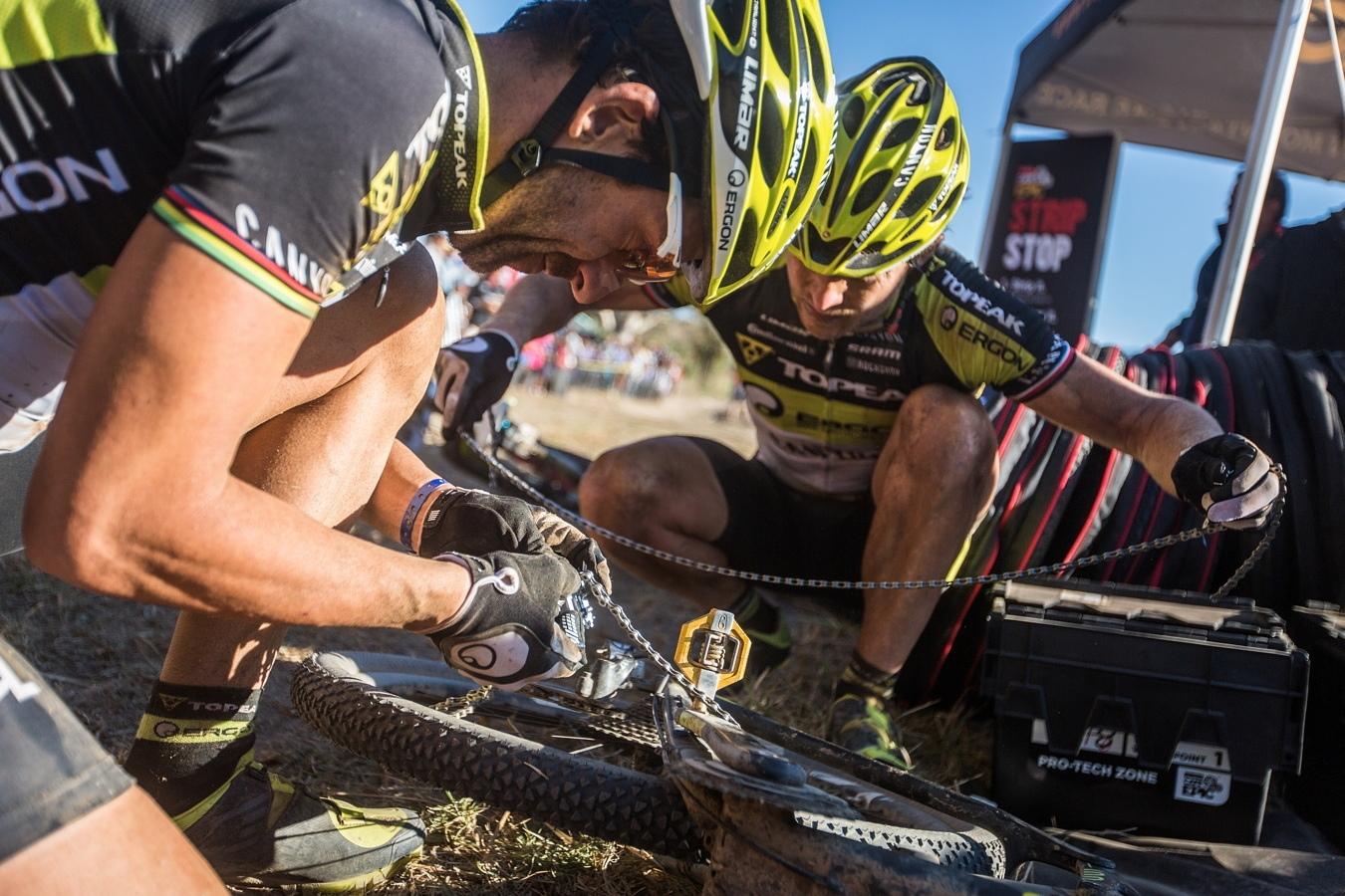 Kristian Hynek a Alban Lakata (vlevo) při opravě řetězu během Cape Epic 2015.