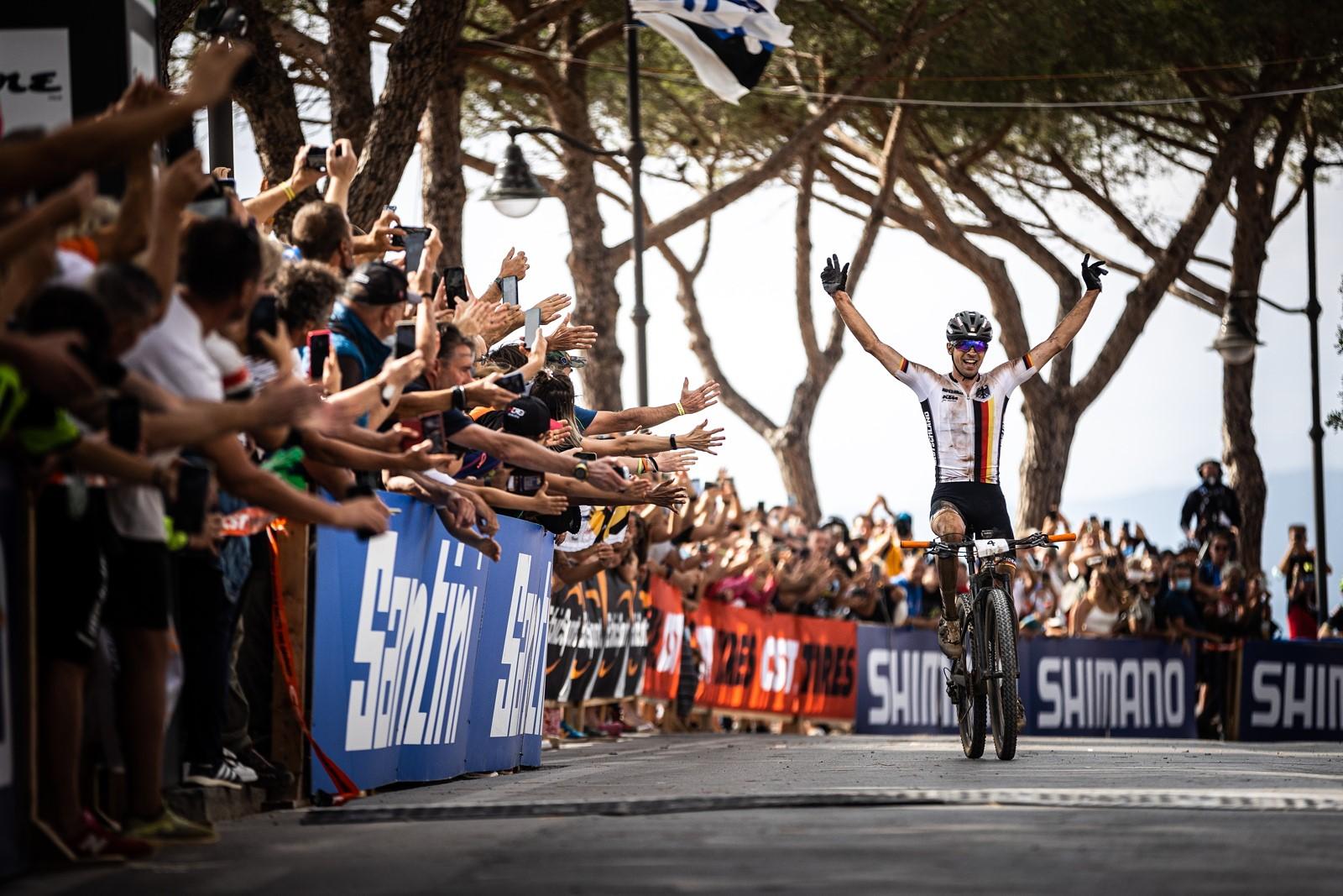 Andreas Seewald projíždí triumfálně cílem mistrovství světa v maratonu 2021.