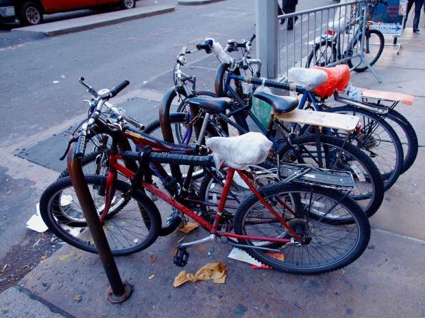Streetworn, well-used bicycles with bag-covered seats chained to a bike rack near a busy street in N
