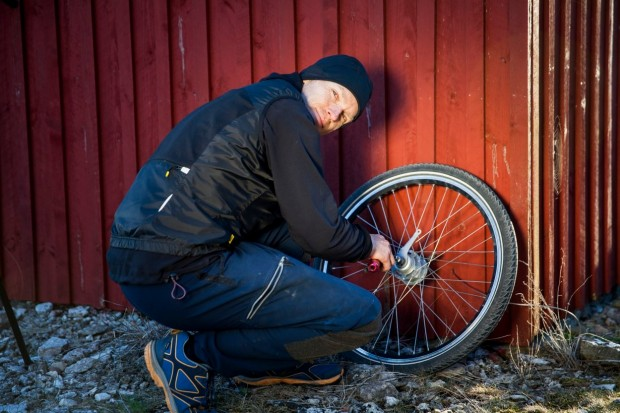 Side view portrait of man repairing bicycle tire outdoors