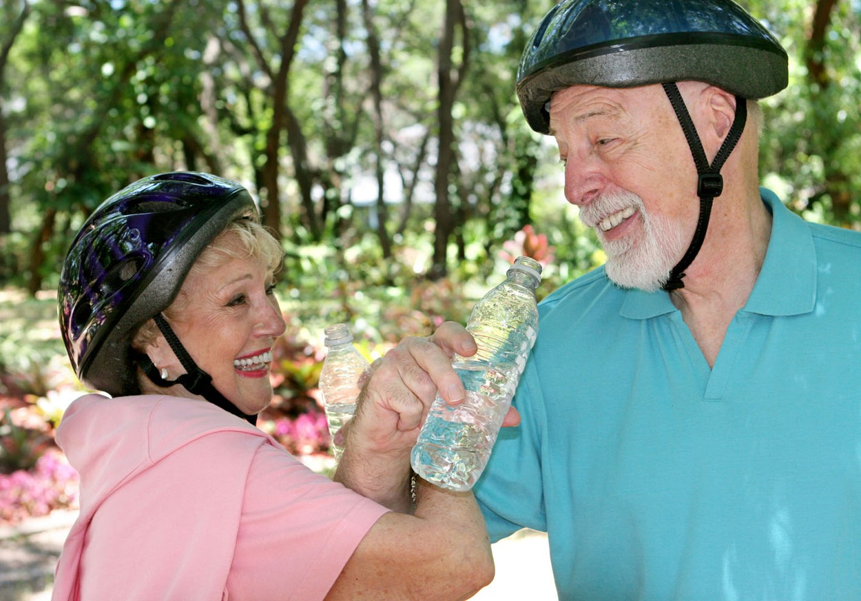 An attractive senior couple joking with eachother as they take a water break during a bike ride