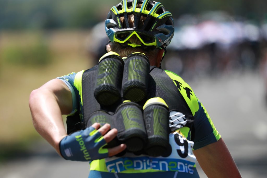 A cyclist of Russia's Tinkoff cycling team carrying feeding bottles for his teammates rides during a sunny day