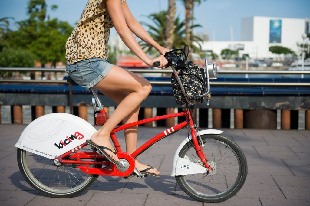 woman rides a bicing community hire bicycle in barcelona